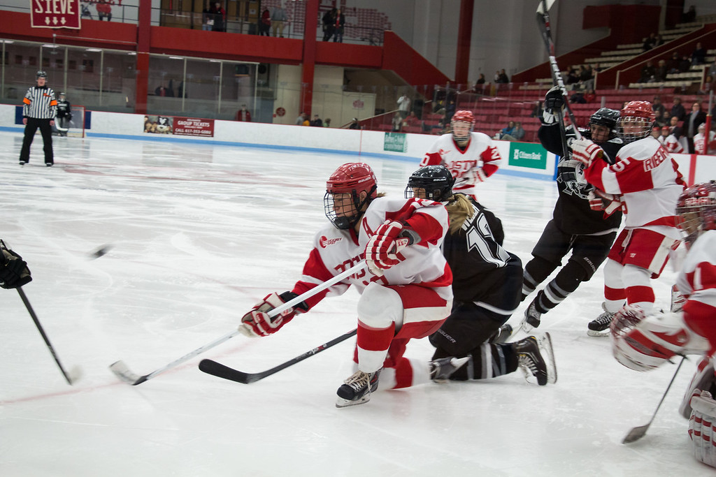 Boston, March 1, 2014 -- Boston University women's hockey defense Kaleigh Fratkin, center, and Providence College women's hockey forward Janine Weber, center right, play during the East Quarterfinals. The game was held at Boston University's Walter Brown Arena in Boston, MA. BU won 3-2. Photograph by Carolyn Bick. © Carolyn Bick/BUNS 2014.