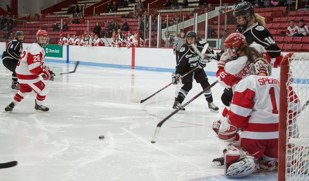 Boston, March 1, 2014 -- Boston University women's hockey forwards Lousie Warren, left, and Meghan Riggs, right, and goalie Kerrin Sperry, front right, play during the East Quarterfinals against Providence College. The game was held at Boston University's Walter Brown Arena in Boston, MA. BU won 3-2. Photograph by Carolyn Bick. © Carolyn Bick/BUNS 2014.
