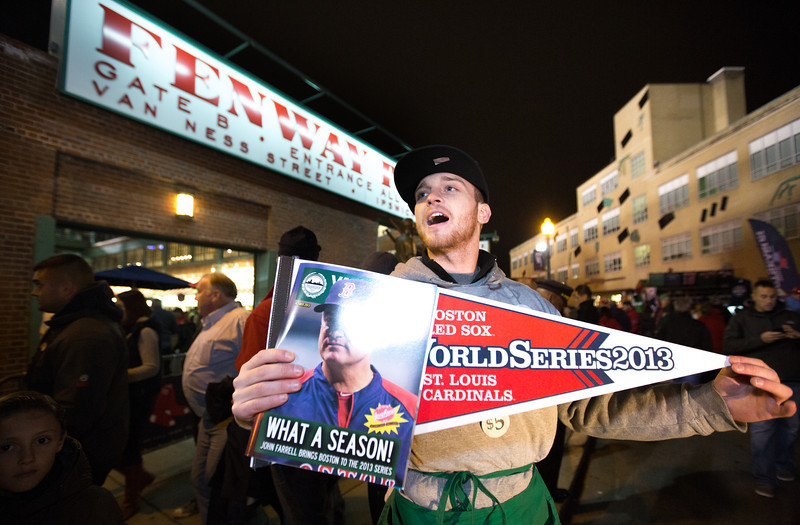 Oct. 23, 2013 - Nick Gray sells World Series pendants and programs outside Fenway Park before the first game of the World Series in Boston.  Photo by Justin Saglio
