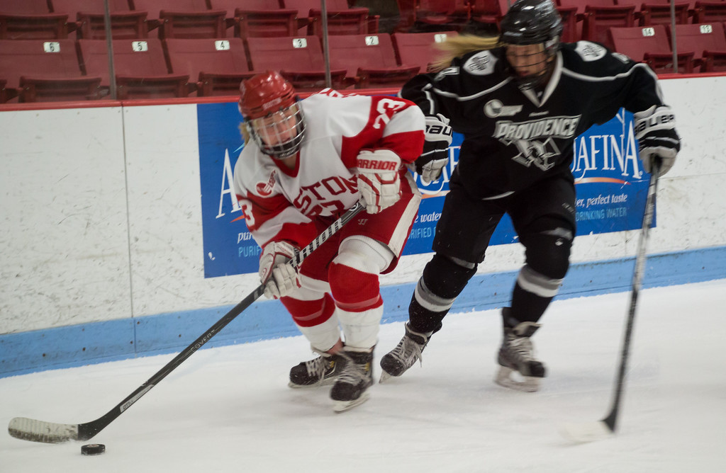 Boston, March 1, 2014 -- Boston University women's hockey forward Sarah Bayersdorfer, center left, and Providence College women's hockey defense/forward Sarah Halvorson, center right, play in the Women's Hockey East Quarterfinals. The game was held at Boston University's Walter Brown Arena in Boston, MA. BU won 3-2. Photograph by Carolyn Bick. © Carolyn Bick/BUNS 2014.