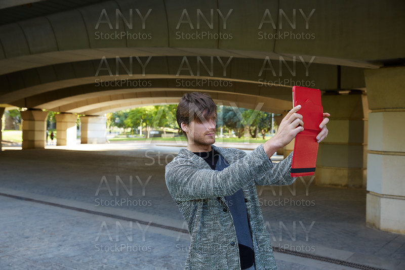 Modern young man with tablet under a bridge