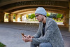 Modern young man with smartphone under bridge