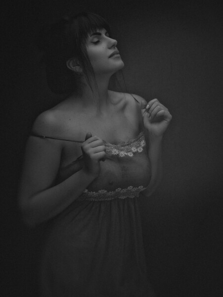 Young adult woman posing against dark background. Grungy female portrait
