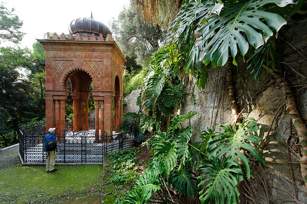 [ITALY.LIGURIA 28981] 'Moorish Kiosk in Hanbury Gardens.'  The Moorish Kiosk in the Hanbury Botanical Gardens is an orientalized mausoleum built in 1886 by the architect Pio Soli. It holds the ashes of Thomas Hanbury, founder of the Hanbury Gardens on the Côte d'Azur near Ventimiglia. The steps leading to the kiosk are flanked by the leaves of Monstera deliciosa. Photo Paul Smit.
