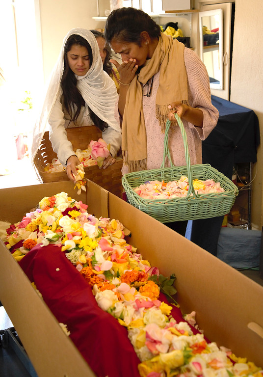 . Soma Sharan, left, and Prabha Sharan, who were both adopted into Sri Ram Ashram as babies and considered Babi Hari Dass their father, lay flower petals on his body prior to his cremation at Santa Cruz Memorial Cemetery on Tuesday. (Devin Kumar -- contributed)
