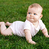 Cute baby lying on her tummy enjoying texture of soft grass