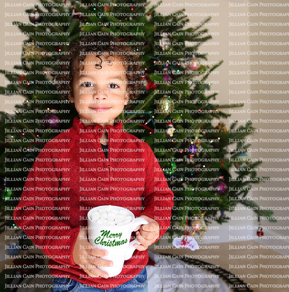 Curly haired bright-eyed smiling young boy standing in front of a Christmas tree while holding a mug that says Merry Christmas.