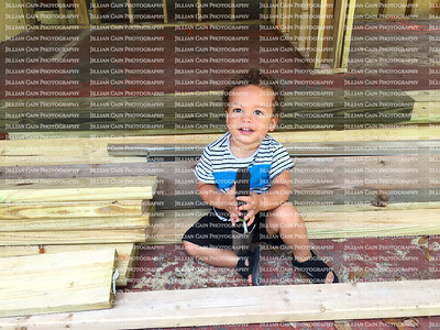 Bright-eyed handsome smiling baby boy sitting on planks of lumber at a home renovation site.
