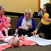 Sheryl White, on right, with Baby Kneads talks with Amanda Davis of Ayer and Britanny Barrett of Leominster as he tells them how to sign to their babies Lyla Davis, 2 months on floor, and Charlotte Darrett, 3 months at the Leominster Public Library on Tuesday morning. SENTINEL & ENTERPRISE/JOHN LOVE