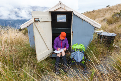 Female tramper writes in logbook at Adventure Bivouac