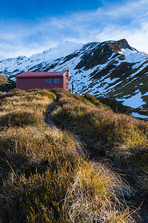 Female tramper outside Liverpool Hut, with Mt Barff behind, Mount Aspiring National Park.