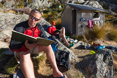 Trampers resting and reading logbook at Adelaide Tarn (Trident) Hut, Kahuarangi National Park