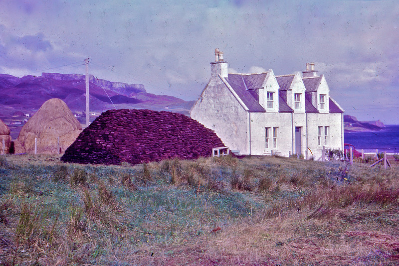 Staffin, Isle of Skye, Scotland UK 1966<br /> Another slide taken by my Grandmother on a European Holiday 1966 and scanned by me 44 years later.<br /> <br /> Next to the house is a huge pile of peat - sods of earth cut out of the bog and dried to burn as fuel. Still used in the Highlands of Scotland but not as extensively as before. It's rare to see a stack as big as this one any more.<br /> <br /> Huge thanks to Fraser P for identifying the locations of my Scottish uploads and the information regarding the peat pile.<br /> <br /> © Phyllis Marjorie Graham Collection