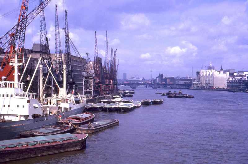 This is a real piece of history. It's a view up the Thames in central London, probably taken from Tower Bridge. The thin tower in the far distant centre is the Post Office Tower, which must have been only just completed in 1966. The other dark square tower to the left of that will be Centre Point, again fairly new at that time. The nearest bridge is London Bridge. The docks on the left are now completely gone. All that mercantile activity has vanished from this part of the river and that part of the South Bank is now covered in shiny glass office buildings including the Greater London Authority building. The WW2 battleship HMS Belfast is now moored as a permanent tourist attraction just where all the cranes are. The Tower of London will be just out of shot on the right of the photo.