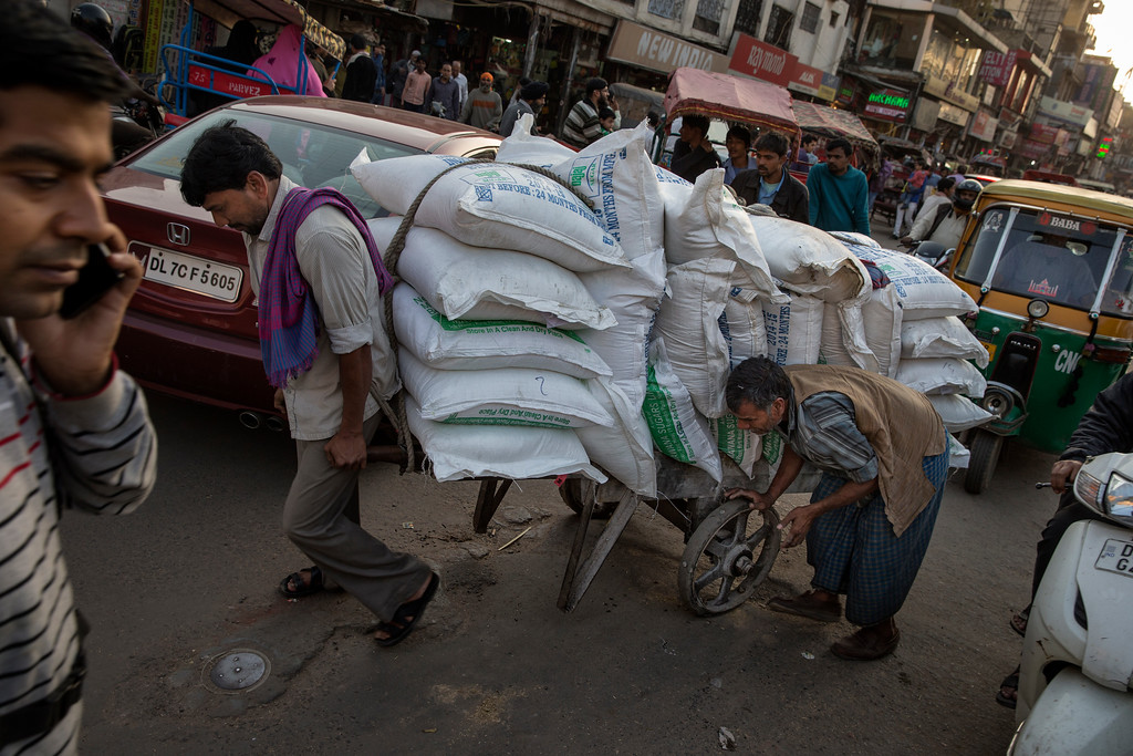 Men pulling heavy load through the streets