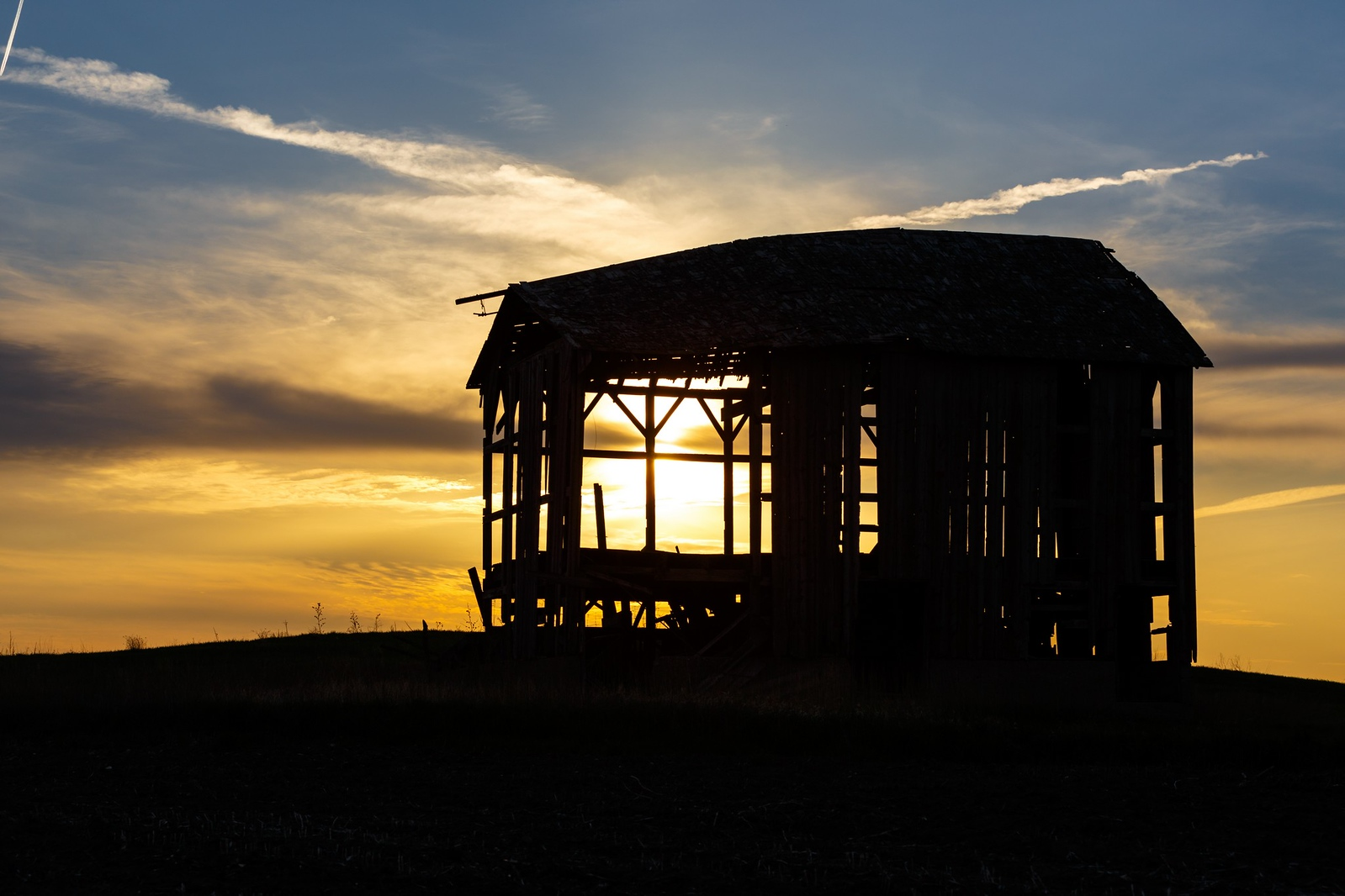 Sunset through a crumbling old barn