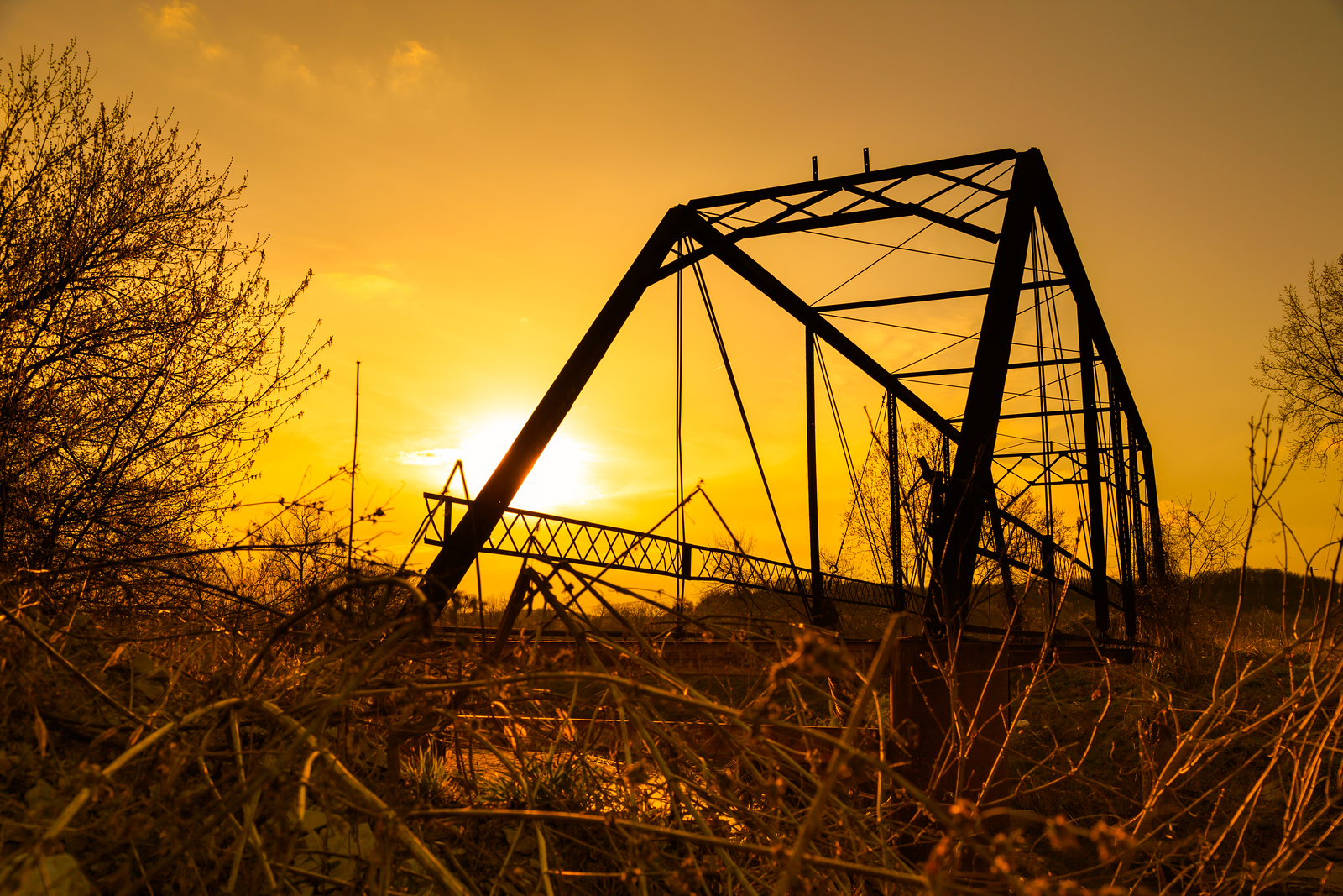 The skeleton of an old rural bridge from the late 1800s stands defiant in the late spring afternoon hours