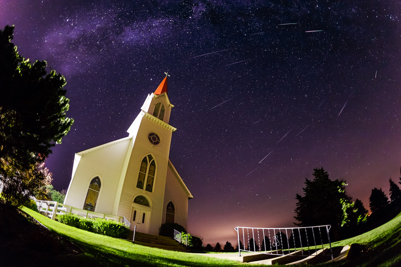 The Perseids meteor shower streaks across the sky over a rural Iowa church