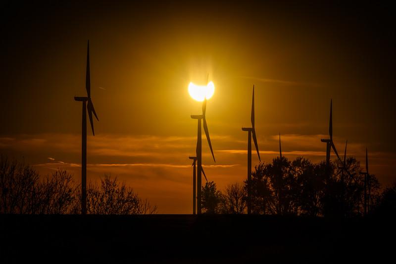 The partial solar eclipse through a wind turbine farm