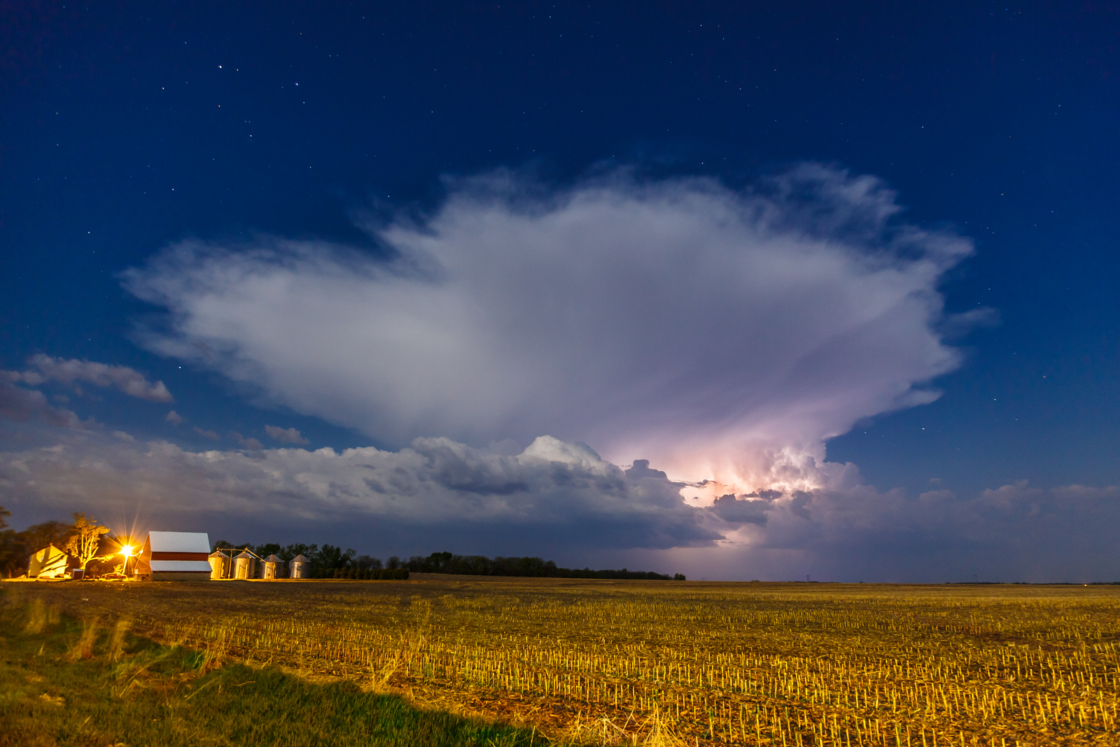An approaching thunderhead glows in the light of a full moon