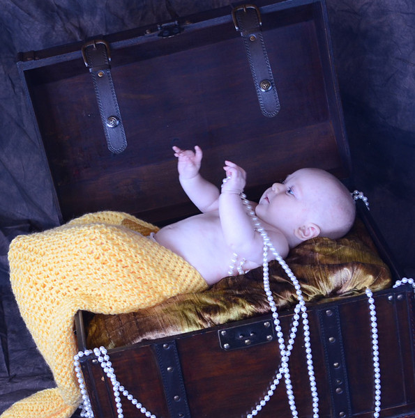 Hand-knit, baby mermaid tails in yellow and green, treasure chest and assorted faux pearl strands.  (Modeled by 3-month-old Bridget.  Mermaid tails made by Jodi Burling.)
