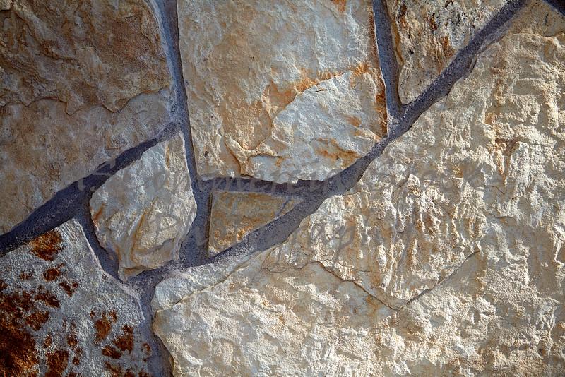 Stone Veneer Natural weathered split flat granite mortar rock wall closeup