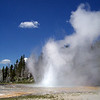 Grand Geyser puts on a show with the sound of small explosions and water shooting into the sky.