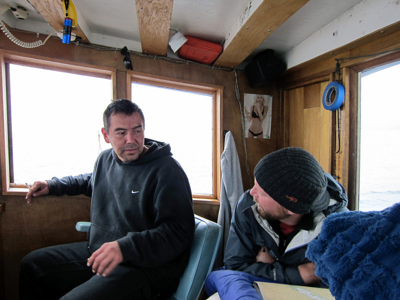 Captain Larry and greenhorn Chad talk in the captain's cabin up top during the passage.  Notice both the pin-up photo and the rosary, hanging side-by-side near the captain's bunk... covering all the bases on long seaward trips in a fishing boat.
