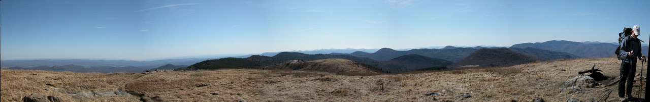 Panoramic view looking southwest from the summit of Black Balsam Knob. John (who was standing next to Steve) anchors the right side of the picture. Sam Knob is the double peaked mountain in the mid-ground to the left of him.