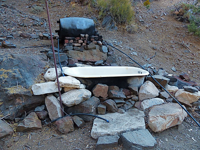 Outside was an old bathtub. Visitors often heat up water in the tank behind the tub and take a hot bath.