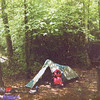 """Trip 21 happens in June 2003 and starts on the Pine Ridge trail and returns to Slickrock Creek where I set up the Muir Trail tent by the 10th crossing at a place I call Slisgah Camp.<br /> <br /> TRIP 21  June 2003<br /> **  The Filthy Fishermen<br /> **  The Wet Foursome at Naked Ground<br /> <br /> TRAILS<br /> Pine Ridge<br /> Fodderstack<br /> Crowders<br /> Big Stack<br /> Slickrock<br /> **Slicnic**<br /> Slickrock<br /> **Slisgah**<br /> Slickrock<br /> **Slicnic**<br /> Big Fat Gap<br /> South Lead<br /> Four Mile Ridge<br /> **Naked Ground**<br /> Four Mile Ridge<br /> **Bob Bald**<br /> 54A North<br /> Pine Ridge and OUT<br /> <br /> <br /> DAY ONE<br />  AFTER A 7 MILE HIKE with full pack I am now sitting along Slickrock Creek near the Big Fat terminus on the Tennessee side of the creek. Several hundred yards upstream and on the North Carolina side is a camp with tarp, three thermarests and several empty beer cans. I will pay a visit later when they return from their dayhikes. I took the usual Pine Ridge/Benton MacKaye and Big Stack Gap trails to reach this spot and Shunka had a full load too and is glad to be stopped. The Warden's Field lot was full and I left my truck next to a camp of very questionable characters, I can only hope it is safe. My """"boots"""" are a pair of 25 year old white leather Nike running shoes retrieved from my Dad last month and they look golfish and lame but they work. The empty camp I saw filled with three fishermen as they walked past me to their clear plastic tarp covered camp. Now I understand the beer cans. I wonder if one of them was the fisherman I saw during my last trip here, the same spot and the same too for me.<br /> <br />     THERE IS NO REAL appetite for food so I snack and fix tea. Sleep will come soon and tomorrow will bring another hike. Today looked like rain and so at Crowders I put on the rain cover and it did lightly sprinkle though not enough for the cover. Now at dusk the sky seems mostly clear and the tent si"""