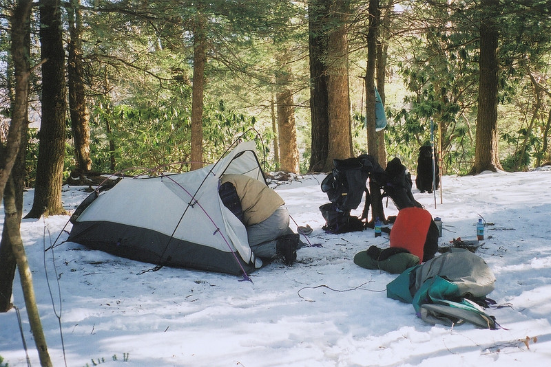 Our December 2002 trip starts on the Pine Ridge trail in Citico wilderness and climbs up to Fodderstack Ridge where we do a nighthike past Cherry Log Gap to this 4,500 foot high site I call Snow Camp.  On the morning of Day 2 I prepare to strike camp and pack up the gear.<br /> <br /> TRIP 15  December 2002<br /> **  Little Mitten Does a Nighthike to Snow Camp<br /> **  Mitten's Brush Mountain Hell Trip<br /> <br /> TRAILS<br /> Pine Ridge<br /> Fodderstack<br /> **Snow Camp**<br /> 54A North<br /> Bob Bald<br /> Four Mile Ridge<br /> **Naked Ground**<br /> Bob Bald<br /> 54A South<br /> Cold Gap<br /> Trail 149<br /> Brush Mountain <br /> **Brush Trailhead Camp(on South Fork)**<br /> South Fork and OUT<br /> <br /> JOURNAL<br /> DAY ONE    Little Mitten and I parked at Warden's Field and walked up the Pine Ridge trail to the junction with the Fodderstack and took the right long uphill climb and then down. It was cold and there was much snow on the ground while we walked past the pretty hemlock site where we camped before last year. We walked and walked in the snow and darkness fell and we used our flashlights to get through Cherry Log Gap and the last trudge up to Snow Camp, the open tentsite, to camp in the cold snow and wind. Three other backpackers in two tents were here from Atlanta and one had a Hilleberg Akto. Mitten used my Marmot sleeping bag on this trip. In the morning we all talked and the boys took off down the Fodderstack to Big Stack and the Slickrock and out Big Fat Gap.<br /> <br /> DAY TWO    We packed and headed up the Fodderstack to the Bob tee where we took a break and then had a pleasant level walk in fairly deep snow to the summit of the Bob. We took a long break in the grass and saw a few other people, then we continued on the Bob trail and down to Naked Ground where we camped. I set up the tent and we did a dayhike to the Hangover. Beautiful.<br /> <br /> DAY THREE    This was Little Mitten's Hell Day so see attached notes. We packed at Naked Ground and headed up the ice and snow back to the Bob. Along the way we saw three hunters with Army ALICE packs coming down. We breaked on the Bob and then we continued to the tee and down to Cold Spring Gap and saw Jody Brown and a friend from the Little River backpacking store in Maryville going past us. We rested at the gap and saw three women dayhikers going up, then we walked down Cold Spring Gap trail to Brush Mountain trail and down it. It became a very hard trail to follow and I lost it once or twice. It was a long and arduous thing but we finally made it to Ikes Creek and then really hurt our legs and feet walking down the steep mountain and on the creekbed rocks. Long story short, we made it with little light to spare to the South Fork of Citico and camped by the Brush Mt trail jct.<br /> <br /> DAY FOUR    We packed it up and crossed the South Fork using a cable and log bridge Mitten discovered. A short walk and out to the truck.<br /> <br /> Tipi Walter