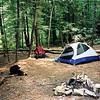 I decide to set up at Big Pine Camp in the middle of the Bald River wilderness.<br /> <br /> JOURNAL TRIP 47  <br /> <br /> DAY SIX<br /> <br /> TRAIL  Brookshire Creek/Holly Flats/Bald River<br /> CAMP  Big Pine<br /> <br />  MORNING ON THE BROOKSHIRE AT HORSE CAMP: Midnight comes to camp as the singing creek puts me in a relaxed mood. What comes next? I just may stay put all day today and linger in the basecamp mode as what are my options, going up the BMT to Sugar Mt where the weeds and briars will again be high?<br /> <br />     I am up and thinking about going up to Sugar and points elsewhere, perhaps to camp on Rainbow Trail, or I just may stay here, whatever!<br /> <br />     I decided to hike into the Bald River wilderness and camp again by the holy water and so while I was packing up 2 dogs ran into camp and then 2 dayhikers came in, a guy and a girl, youngish but we sure didn't talk much. It is therefore time to move!<br /> <br />     I left the Upper Bald tentsite and walked over the creek where I met a friendly fisherman from Florida. I now sit at the Holly Flats turnoff resting and checking out the bridge and people camping.<br /> <br />     Here I sit on the Cascade rock with 14 members of the Tennessee Trail Association dayhiking the Bald River trail. I am tempted to swim here and I just might. Naw, I left the crowd and the rock and breezed past 3 fishermen before I settled here at beautiful Big Pine Camp where I set up the nylon tipi and quickly jumped in the river with my soap to bathe.<br /> <br />     Yippee to all who pass as this is a perfectly friendly campsite and the best one I've been at since this trek began. The Six Mile Gap site was homemade, small, dry and bugfilled. The Unicoi Rolling Stone site was another homemade place where I had to pull weeds and move sticks for 30 minutes until I had room for my tent though in the end it became a very nice though bug filled site close to flowing spring water. Horse Camp of course is always nice an