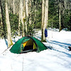 Bright snow pictures are the best, especially when showing off a new green Hilleberg tent.  It's the Staika at 8.3 lbs and just perfect for the solo backpacker.<br /> <br /> JOURNAL TRIP 55<br /> <br /> DAY TWO<br /> <br />   MORNING ON THE SOUTH FORK TRAIL: The dogs are curled up around and about the Kerlon green tipi and the weather? It's a cold wet miserable dark night with dripping trees and a thick mist covering everything including the tent. Daylight might provide relief or it just might spell disaster in the form of cold, wet, miserable conditions for packing up and moving out. It isn't raining per se and if yesterday is any indication there will be patches of blue and sunlight for awhile before the rains of late Tuesday come calling. My goal is to wait it out and move forth when I'm good and ready as my next hike will be only 5 miles up to Iron Camp and a gain of some thousand feet to the snows of 3,500 feet. Beyond that will come a mean hump to some true high ground and aptly named Snow Camp.<br /> <br />     It is day and time to get water for tea so let me get up and stretch. Ok, breakfast is over and consisted of hot nettle tea with manna bread. Now I am quietly considering packing up and climbing to the Iron Camp site, it'll be slow going with a full pack.<br /> <br />     ON THE SOUTH FORK TRAIL: Ok, I left Eagle Camp in the cold fog and pulled the first section and stopped to remove my balaclava and hood to begin the short but steep next section up to the cut and past it to the ditch and the start of section 6 of a 14 section trail. My trail food of choice today? Purple cabbage while I'm moving and a sandwich while I'm resting. Landon the stray dog is still with us and has a lot of energy as he runs up and down the trail. He looks abandoned though there is a tag with his name and phone number on it. He is starving but we have no food to spare this early in the trip. When I got to the Fields there was a truck parked nearby with Blount county tags and i