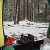 This view out the tent door shows the snow and the Fugitive Asolo boots and the red crocs and a pair of alpaca socks.