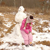 The little kid loves the snow and likes her snowman.