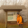 I study the kiosk map and I'm ready to start a New Year's trip!<br /> <br /> JOURNAL<br /> <br /> DAY ONE   TRIP 129<br /> <br /> TRAIL: Huckleberry Knob<br /> CAMP: Side of Huck Knob<br /> <br /> A NEW YEAR ON THE MOUNTAIN KING<br />     I wish all my readers a very good New Year and hope they find---we find---some expression of the outdoor world we can include in our lives. I hope we are able to continue our pursuit of the wild natural world and we are able to develop our relationship with Miss Nature, the woman of the green and blue and brown and white, the woman of the wind. 2012 may be the last year for some of us and if so I hope the transition is without fear and our loved ones are waiting for us on the other side along with our dogs. If 2012 proves to be our final year, let's go ahead and be thankful for the trips we've done under load and for the spectacular things we've seen on the mountain ridges and inside the clean creek valleys. Thank God we made it this far and thank God we've been able to hike on two legs with a pack. There is much to be thankful for.<br /> <br /> ON THE NEW YEAR'S SUMMIT OF HUCKLEBERRY KNOB<br />     Little Mitten and I drive the Toyota up the Skyway into a world of thick fog and rain and high winds. We have to slow to 30mph just to see what is up ahead. The grand plan for the trip requires we go past Beech Gap and we do so passing Hootyhoo's blue van on the way. I want to get out and start my trip there so as to see the Hoot but my pack is stuffed with maps and ribbons for a long swaray into the Snowbirds so we keep on and in eight miles pass the Hooper Bald pull off and continue a short distance to the mighty Huckleberry Knob trailhead which leads to the highest mountain in the Cheoah ranger district at 5,560 feet or basically 5,600 feet, 300 feet higher than the Bob.<br /> <br />     We take the necessary photos and we say our goodbyes and I load the anvil pack onto my back and start climbing up to the first little bald which is 