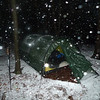 "The best pics are at night in a snowstorm and so Low Gap gets pelted with the white stuff and it's about time.<br /> <br /> JOURNAL<br /> <br /> DAY SIXTEEN   TRIP 141<br /> <br /> TRAIL Big Frog<br /> CAMP Low Gap<br /> <br /> GETTING OFF THE FROG<br />     A big wind storm is coming as I'm up at 6 in the morning and got thru a night of constant rain which is gonna turn ugly by this afternoon so I gotta get off the mountain pronto before everything freezes up and turns nasty. I'm into my 164 hour of rain and it's damn hateful and has ruined this trip but there's nothing I can do about it. Today is the time to panic and move at all costs in a butt cold wind with slicing sleet. Wish me luck. First light and I'm gone. I'll wear whatever I feel like wearing. The Knox wee'tards are even calling for 3 inches of snow beginning at 2pm so you know old Frog will get walloped---the point is I'm 10 miles from evac in 3 days and can't be stymied with postholing or frozen trail ice and so I'll probably pack early around 9 and hoof it off the mountain on the Frog trail all the way to FS 221 and pull a mile on it to the BMT and turn right down it to my usual camp on the West Fork of Rough Creek.<br /> <br />       If this storm hit earlier in the trip I would sit put and be happy and hell I still might but I need to pack a so far ice-free tent and pull a zero off the mountain and get relief by losing a couple thousand feet. I'll still see snow but not as much and not nearly as much wind. This is a real winter storm folks and the Bob would be the place to be but no thanks. The Frog is sufficient unto itself. I hate hiking in a butt cold rain but I have the gear to do it and this is how it plays out---<br /> <br /> ** Pack up everything in the pack while still inside the tent.<br /> ** Wear rain pants without merino bottoms (gotta keep them dry).<br /> ** Use old socks and keep the other pair dry.<br /> ** Keep on merino tops and fleece hat and don Arcteryx rain jacket.<br /> ** Allow one pair of fleece gloves to get wet cuz they'll be worn.<br /> ** Once pack is ready throw it out of the tent and cover with pack cover.<br /> ** Roll up inside ground tarp and pull all stakes and take down tent quickly.<br /> ** Stow poles, stakes and tent and put on pack.<br /> ** Cover pack completely and get the hell out of Dodge.<br /> ** Oh, and stow important lid items in ziplocs and put camera in lid too or put in ziploc and leave in rain jacket chest pocket.<br /> <br />     There you go---I'm set to move and it's all downhill. I've got the full leather boots for it and about as ready as anyone. I don't need to be pinned here into late Friday and definitely not into Saturday. Right now the rain isn't terrible although the tent is soaked so it won't be light and my hands will freeze solid at take down which ain't good. The hiking itself will be easy and fast and I'll remove my top layers if need be. It's now right at freezing or close to it so the hands will suffer the most. Maybe by 8 or 9 I'll get a window and a lull of no rain, just maybe.<br /> <br />     I hope Christine Thuermer is off the trail by now as this is very nasty weather. Thankfully I know my route and I assume the Big Frog trailhead on FS 221 will take me to the BMT as it crosses 221 which I know well. A left and I'm back at Thunder Truck, a right and I'm on Rough Creek, a raging Rough Creek. Hell, after all this rain the entire campsite could be gone.<br /> <br /> 9:30<br />     The rain just won't stop so I'm not going anywhere, in fact the rain is coming down about as bad as any time in the trip and it just won't let up so I'm gonna let Miss Nature decide my route and my schedule and not do something stupid and bail off the mountain in a butt cold rainstorm. Right now it's just rain, soon it will become sleet and snow. By morning I'll have 8 to 10 inches of snow and a frozen stiff tent but all this is supposed to stop by 9pm and be clear, cold and sunny tomorrow which is maybe the best time to bail unless this true crap ends and gives me a chance. I do have 2 days to get to Thunder Truck starting tomorrow morning so maybe I'll be brave and crazy and sit put like the motarded basecamper I am.<br /> <br />     Other folks? Fellow backpackers? Sheeeet, they're all huddled up in beds with television remotes greased down with crisco and stuffed in various orifices while shivering inside 75F degree houses and weeping over the latest weather reports while on a hotline with the suicide prevention center cuz they sure as hell ain't out here in the vaunted Big Frog wilderness. All my fellow hikers and backpackers and all NC boys and Georgia boys and TN boys of the nylon cloth are somewhere else today and tomorrow and for the last 2 weeks so it's up to me to file the trip reports in conditions which cause most all backpackers to look out their windows and nix yet another weekend trip because Miss Nature is too freaky and too unpredictable and too serious. I agree, but can verify better since I'm out in it.<br /> <br />     9:40---the rain really pelts the tent in a heavy cold deluge and there's no hope and no way I'm hiking in this sea of stool. Luckily my top o the Frog campsite is not underwater as there's only one place for water to go and it's down and away. There's a little tan spider up in the apex of the vestibule sleeping and I wake him up with a touch to the face. He jumped alittle and went back to sleep. I can't allow him to die when I pack up cuz I'm a lonely sentimental bastard and he's the best friend I have and he's out here with me more than I can say about other humans. He's okay now but won't like it tonight when the temps dip to the teens. Glad I burned the trash when I did.<br /> <br /> COYOTE NIGHT<br />     Very early this morning a coyote passed thru and howled periodically and he came close to the tent and we talked. He told me his usual routes are blocked by high water so he has to stay on the high ground. I told him it's gonna get worse and he took off. Where do these guys go in this crap? I imagine there are a couple hundred coyotes and bears all shaking off water thruout the wilderness like random twinkling stars. They don't have gtx or rain coats except they have water shedding fur which has to be shook frequently and I imagine the best of them have rotten logs and dens and rock overhangs to sit this storm out, otherwise there'd be a Hilleberg tent full of possums and bears and coyotes and raccoons all squeezed in together calling a truce between mammals and humans. At least when the snow comes this damn rain will stop and good riddance.<br /> <br /> WINTER WEATHER ADVISORY<br />     The wee'tards are cupping each other's balls and huddled in a closet weeping as up to 4 inches of snow may fall today but the Chattanooga folks could give a crap and I feel the same way.<br /> <br /> SOUR DRAWL<br />     It's a woman country music singer and it's hard to listen to and hard to listen to her voice. There's a nasal twang which is like a blow to the head; I sit concussed. The song and the singer? ""It Happens"" by Sugarland. Of course you could say that listening to Janice Joplin is like having your scrotum rubbed raw with sand paper. She would've made a great country singer.<br /> <br /> SUNLIGHT LET UP?<br />     It's hard to say and don't be fooled, Miss Nature is like a cat waiting for the mouse-hearted Wally to stick his head out of the tent and POW!! Claws to the frontal lobe.<br /> <br /> 3.2 MILE BAIL<br />     Nothing changed rain-wise but Momma Nature threw a lone light beam into the tent and it woke me up to the possibility of packing the wet tent and gear and getting the heck off Frog Mt---a wise decision as it allowed me to lose almost 2,000 feet and while not keeping me snow free at least it puts me in a more gentle world at a campsite in Low Gap. Just after getting set up and getting water down at the spring (which is now a raging river), a new rainstorm hits the tent so it's 174 hours of the stuff. Rain has become sleet. When I bailed off the mountain I had a long line of mammals following behind and for good reason as they want off the mountain in the worst way.<br /> <br /> IN HIS CASE IT'S A PINCHING WORM<br />     It's wet and cold and sleet is everywhere so god knows what's coming tonight although the head entrail-handler wee'tard says it's all supposed to end by 7pm. I think in his case he has a pinching worm burrowing into his brain and is being forced to say this without clear thought. If his whole production team have these worms then no one will stop him as his broadcasts go out to the public. Once this worm reaches his medulla he'll quickly panic at any temps below freezing and as the worm eats its way down his spinal column he'll quit his job and plunge into sewage looking for the mother worm. Once united, he will be encased in a clear hardened fluid as a suspended egg sac and given time to rethink his predictions. A blast of cold mountain air will split open his transparent sac and he will tumble out into the weather studio where all this started.<br /> <br /> LOW GAP CALL OUT<br />     I try to get Little Mitten but have to leave a message instead and then put the phone back in the pocket of my down parka to keep the batt warm. The sleet has turned to snow making a tinkling sound against the tent, a new sound after 178 hours of rain and a welcomed sound since the storm blew in with mean gusts and I had to go out in it and put in the 6 guyline pegs. Now there's nothing left to do but stay warm, stay supine and stay dry until a sunny day tomorrow whereupon I'll pack and finish the Big Frog trail as it ends on FS 221 at which point I would've done the entire Frog trail. On Day 4 and 5 I was on the trail and then Days 8-9-10-11-12-13-14-15 and 16 (and soon to be Day 17) so you know how bad the rain has been.<br /> <br /> GLOBAL WARMING?<br />     Maybe planet warming has made having a simple winter storm almost impossible to achieve even in January without a preamble of 8 days of rain beforehand to punch it out like a giant baby from a tiny womb. 18 days in a Big Frog rainstorm my obituary will read. Something ain't right but then it's like a line out of Saving Private Ryan---when's the last time you had a good feeling about anything?<br /> <br /> TAKING SNOW OFF THE TENT<br />     I go out at 9pm and move the snow off the tunnel tent.<br /> <br /> TRIP SUMMARY<br />     It's easy to summarize in one word---Rain.<br /> <br /> 182 HOURS OF RAIN---MIDNIGHT<br />     Before the rain though I actually had blue skies and low creeks and got to run into the German Tourist which made my day and I got to explore trails never hiked like Wolf Ridge and Yellow Stand lead and Grassy Gap and the complete Big Frog. Then the rain hit on Day 8 and 9 days later it becomes the most main component of the trip but at least I got some snow! In fact, I need to go out and take a flash pic of the tent so let's do it. Tomorrow I will pass Rough Creek jct on my way out to FS road 221 and from here to the road is 2.4 miles on easy trail. After reaching 221 I will turn right and go .5 mile to FS 45 jct and another .4 mile to the BMT/West Fork trail 303 as it crosses 221. Then I will probably turn right and head back down to my camp on Rough Creek where I started this trip. It will leave me a 4.4 mile exit to Thunder Truck and my evac ride with Little Mitten. I gotta remember to pick up my cache on the way out.<br /> <br /> ANXIOUS TO MOVE<br />     Yup, I wanna pack and explore more new routes but it's 10pm and I gotta wait.<br /> <br /> <br /> Tipi Walter"
