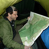 """Day 14 is a day to shake off the doldrums of lonely soloing as Patman shows up and pulls a 3 mile nighthike on the Big Frog trail and comes into the tent as we study our maps.<br /> <br /> JOURNAL<br /> <br /> DAY FOURTEEN   TRIP 142<br /> <br /> ZERO DAY<br /> <br /> THE MIDNIGHT MAELSTROM<br />     It's the biggest storm of its kind since I was here last 8 days ago in Yes another windstorm which was so bad I barely got the tent set up and staked. This storm is worse because it's on-going and long-lasting and of course it has a cold rain which pelts the tent sideways and wants inside so bad it doesn't know what more to do. """"Keep out!"""" I shout. """"Bugger off!"""" says the tent. """"Eat pee!"""" we shout and still the rain wallops but does not come in even with a dozen seams sealed and 8 or 9 poke holes glued shut. Praise McNetts and hold on for the ride.<br /> <br /> TOXIC LOAD<br />     It's a unique storm like all the rest but this one's special because it's happening to me right now and not yesterday or last week or last month or last year. As long as the trees stay up I'll be alright, otherwise all bets are off. The bean soup I ate 6 hours ago is killing me and causing my guts to knot up and my back to hurt and only timed farts and an eventual mad rush to drop a turtlehead will bring relief. God knows I don't want to dump a load at this hour and in these conditions so c'mon turtle boys and be a friend and let me be. I refuse to squirt out Young William inside the tent vestibule. But if it's bad enough you'll do anything to dump a toxic load and get as far away from it as possible. Even in a driving winter rainstorm.<br /> <br />     The trees look down and laugh. A coyote hides behind a tree and snickers, maybe eager for a taste. All I know is a big black beetle came into the tent to hide along with a spider and a little millipede. They know it's a'stormin' and they know I got a Hilleberg. Welcome boys just don't get crushed by my silverback gorilla weight. By morning this"""