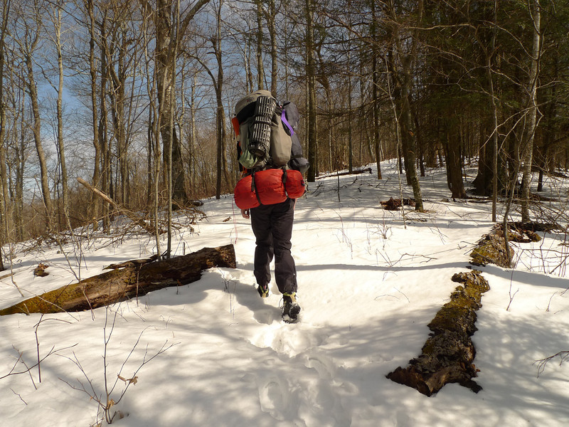 "It's not so easy climbing a thousand feet in 6 to 12 inches of snow but Hoppin John leads the way.  He has a red Hilleberg tent and a Mystery Ranch G6000 pack so we look similar.<br /> <br /> JOURNAL<br /> <br /> DAY TWO   TRIP 143<br /> <br /> TRAIL 54A South<br /> CAMP Bob Bald Raven Camp<br /> <br /> MY ONLY GOAL<br />     The sky remains clear and black with a billion stars so now at 6 in the morning I wait for first light and the brewing of hot tea with honey. The honey is rock hard and is made by Y.S. Eco bee farms. A good burn pile will consume some bookage and 2 book rolls but this won't happen for awhile. It's a very calm night here in Cold Gap. My only goal today is to pack and climb to the Bob, easy enough even with a 75 lb pack. After Hoppin John and I commiserate over our tents we'll split up and I'll either walk him down the trail to Cold Gap and then split up or I'll stay on Four Mile Ridge and work my way to Naked Ground and the Hangover---the usual haunts. I have no grand plan to go or get anywhere except maybe Toad Camp on Haoe Lead and points down.<br /> <br /> HILLEBERG FLAW<br />     The biggest long term flaw on the Hilleberg tents is their use of crappy black elastic connectors between the tent fly and the inner tent. All of the keron elastic has stretched permanently causing the entire inner to sag and there's one elastic band in particular which is completely useless and excessively stretched to the point where it just hangs uselessly. It's their biggest weakness but the company doesn't address the problem. I need to email Hilleberg about it but what can they do? Keep my tent for a month to sew on new elastic? No thanks.<br /> <br />     Here's a solution: get rid of the elastic connectors. Luckily the Keron is big enough inside that even with ruined elastic it still offers enough room for 1 person (even though it's a 3 person tent). This elastic flaw has been present in both my Staikas too and the company's reply is to get sent new elastic and sew them on myself. Too much of a job for 24 connectors and 48 sew points. I keep saying it but these black elastic connectors are an engineering failure waiting to happen as elastic deforms over time and stays permanently stretched and longer which ruins the whole purpose of a Hilleberg tent---to have a strong and firm supported inner tent. What to do? Buy a new tent? Naw, too expensive.<br /> <br />     Go back to the MSR Fury? Naw. Do a home repair? Maybe I will get Hilleberg to mail me a set of elastic and replace the most obviously ruined ones. At first light I'll inspect them and do a field repair whereby I shorten them by wrapping and re-toggling. Hilleberg uses excellent materials except for these elastic connectors. Here the material fails as the whole concept is flawed since elastic is never meant to be permanent or not stretch. Look at high use rubber bands or the waist in your underwear---they all stay stretched over time and Hilleberg should know this when they decide to use elastic. So Hilleberg fails us on 2 basic levels---<br /> <br /> ** Elastic connectors.<br /> ** Stubby length with bag draping angled tent foot-end walls.(But not with the Keron/Kaitum).<br /> <br /> MORNING TURTLEHEAD WITH TEA<br />     Yes, the full sun hits the tent in warm temps and so i begn the day with a turtlehead and then I burn 2 book rolls and get to making 4 bag tea with 2 bags nettle, 1 bag smooth move and 1 bag cranberry. I've got all day to reach the Bob and so it's time to brew tea and slowly pack.<br /> <br /> NEWS<br />     New England covered in 2 feet of snow. The sea is destroying a couple homes.<br /> <br /> HOPPIN JOHN PULLS INTO COLD GAP<br />     It's good to see old Hoppin John as he left Alabama at 1:30 in the morning and 5 hours later he's at Beech Gap and ready with his Mystery Ranch pack and new Hilleberg Kaitum tent. I'm still drinking morning tea as he comes up and says,<br /> <br /> ""Is that squirrel you got on the fire?""<br /> <br /> And I reply, ""Why? Grown par-tick-u-lar??""<br /> <br />     He watches me pack and we trudge up a tough trail in 12 inches of snow to the top of Bob Mt where we stop to talk to the backpacking couple who came in last night and are camped by the Death Tree with their dog Sammy. Here's the wild part---it's the same couple and the same woman who was hornet stung and rescued by the Graham County rescue squad on Trip 138. They were coming up the Nutbuster trail when she got stung and many came in to get her out. She now carries an Epipen. It sort of blows me away to see them up here again after that September crisis.<br /> <br /> BACK TO RED<br />     Anyway let's get back to Hoppin John. He's set up on Nokia Hill and I'm on Raven Top as we prepare for something coming tomorrow and we will sit thru it all---maybe rain, maybe wind, maybe thunderstorms. He brought several items which piqued my interest like an Exped blow bag to attach to my Exped to make pumping easier; an Exped Multimat which is super light and super insulated for an inside-the-tent ground cloth, and of course his red Kaitum tent and a small black plastic ladle---excellent for determining scrotum size and weight but he uses it for soups!<br /> <br /> BACK ON THE BOB<br />     All hell could break loose but it's good to be back on the Bob especially with old backpacking buddy Hoppin John and the dual Hillebergs.<br /> <br /> DARK NIGHT GOODNIGHTS<br />     I swing down to Abbi's camp to talk and say goodbye and then I swing up to John's camp and sit inside his spacious tunnel tent to look at his string of suspended Christmast lights and we talk until my feet get me out and under geese in my tube tunnel. It's time to recap the day in the journal and call it quits with a couple peanut butter cookies.<br /> <br /> <br /> Tipi Walter"
