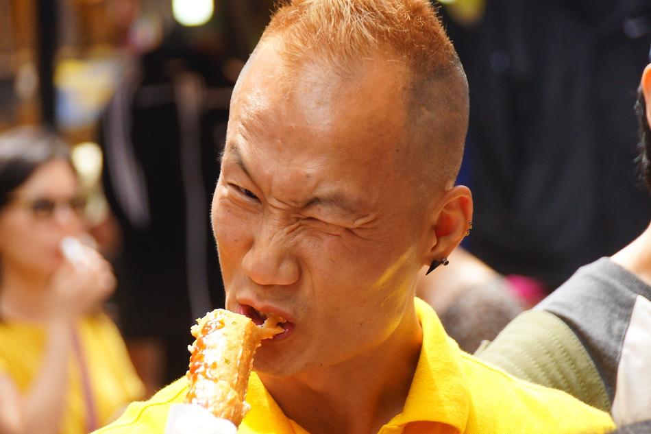 Korean man with a distinct face eating street food in Namdaemun market - Seoul, Korea