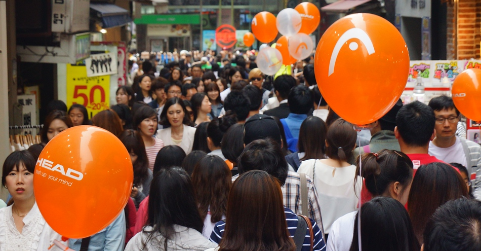 A packed crowd of shoppers in the Myeongdong shopping district area of Seoul, Korea