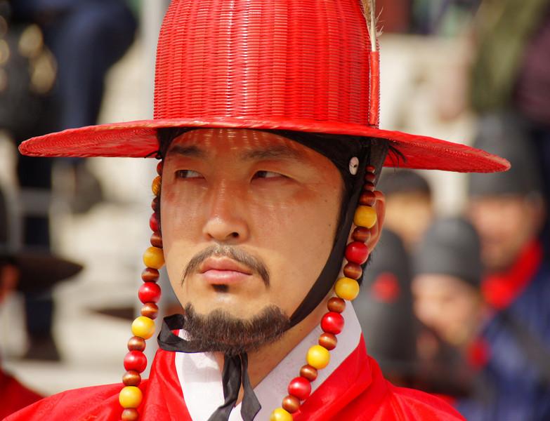 A royal Korean guard wearing a red top hat at Gyeongbokgung Palace in Seoul, Korea.