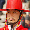 A royal Korean guard wearing a red top hat at Gyeongbokgung Palace in Seoul, Korea.
