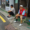 Two elderly Korean men sitting on the curb in Itaewon - Seoul, Korea