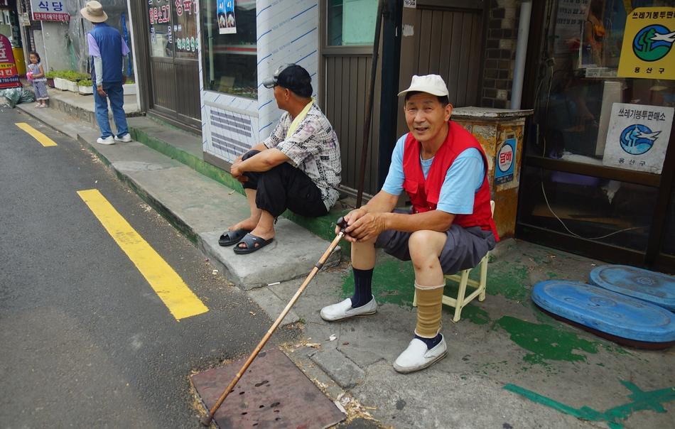 Two elderly Korean men sitting on the curb in Itaewon - Seoul, Korea
