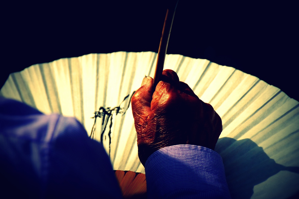 An overhead perspective of a Korean artisan perfecting his craft on a fan.
