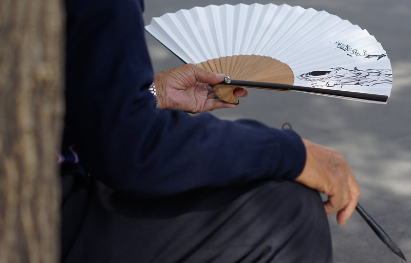 An elderly Korean man sits against a pole on the street of Insadong with a fan in his hand.