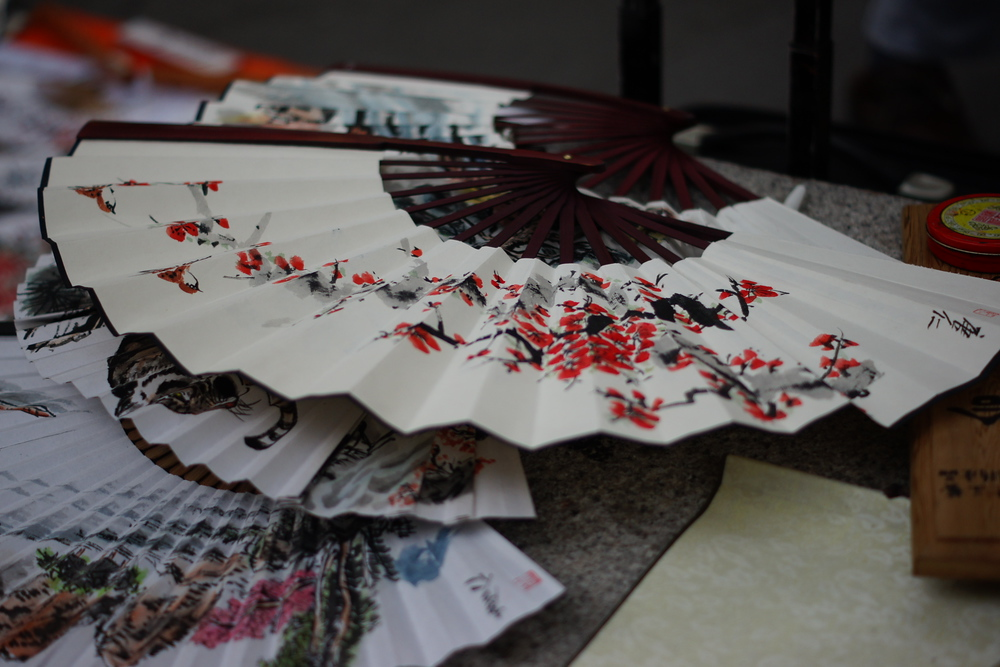 A group of intricately designed Korean fans are spread out along a table on display for sale.
