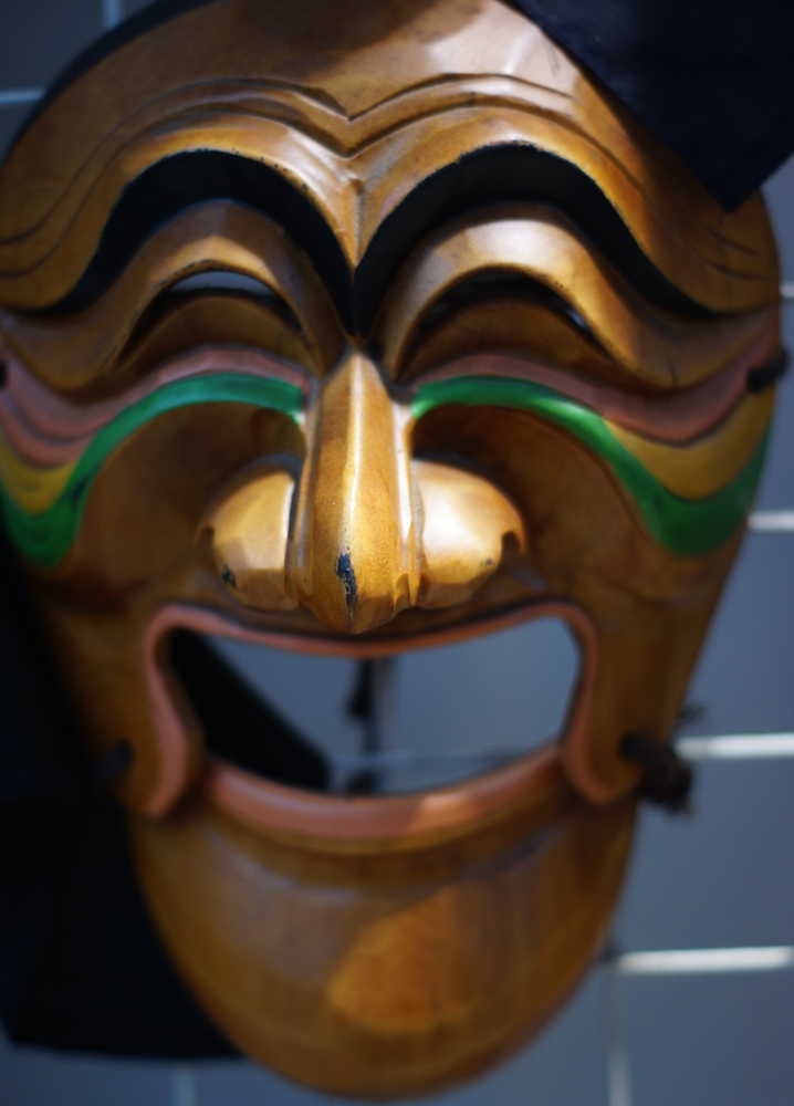This is a Korean traditional mask with what appears to be a smiling face carved out of wood.